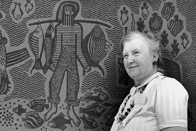 Helen Louise Allen in front of textile