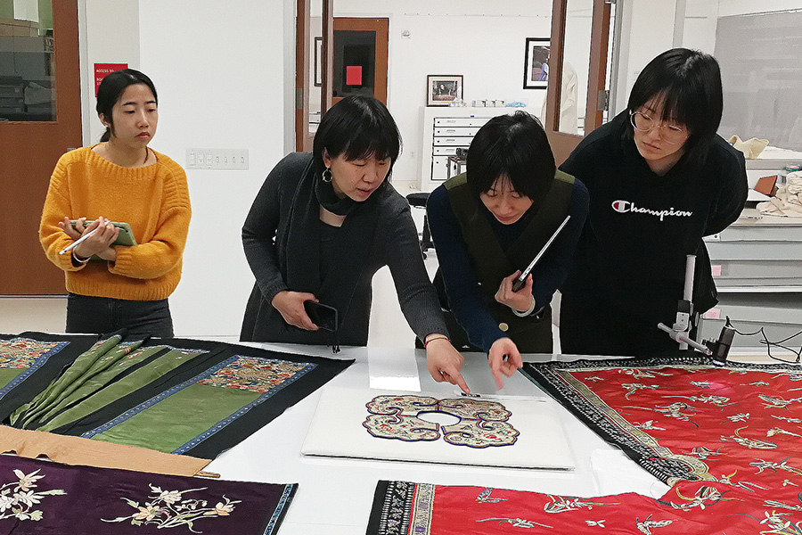 Students in Chinese Textile Course examine textiles
