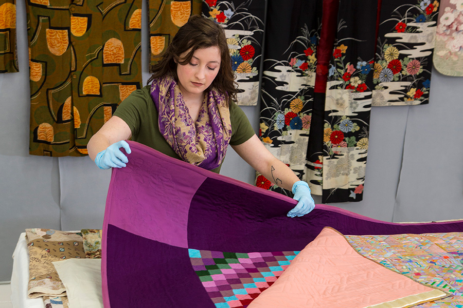 Woman with gloves carefully studies textile objects.