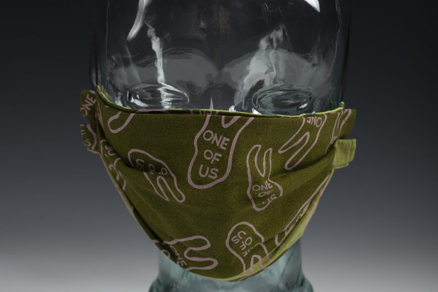"Color photograph of a face mask mounted on a glass head form. Mask is made of a olive green cloth material with printed pink two-fingered hand designs with the words ""one of us"" also appearing in pink text inside the hand shapes."