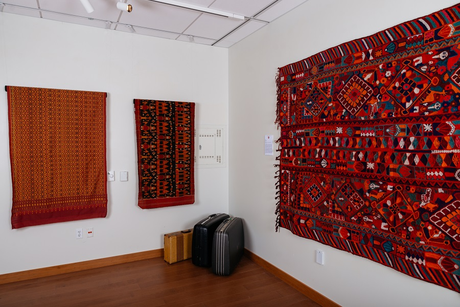 corner of gallery with suitcases and large textiles hung on the wall.