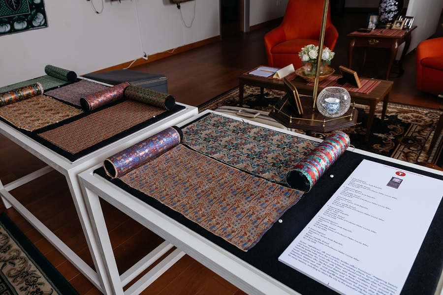 installation image with open display case of unrolled textiles