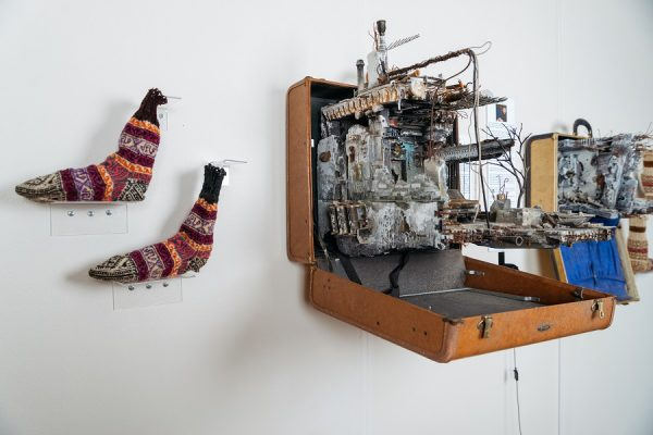 Installation image of UNPACKED in LMTG - one suitcase sculpture and woven socks on white wall