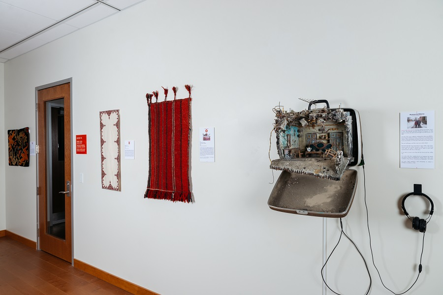 Installation image of UNPACKED with 1 suitcase sculpture and multiple textiles