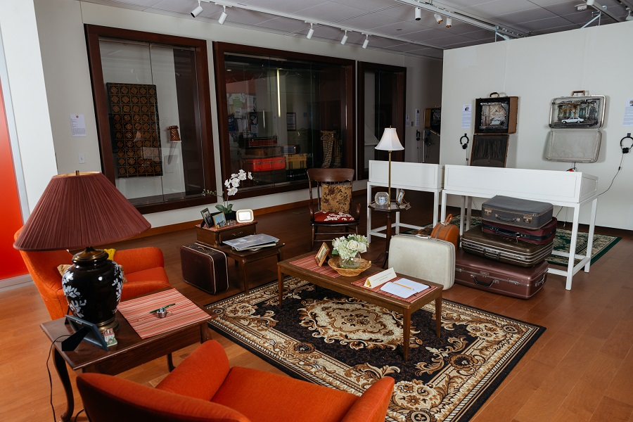 Installation image of a living room set up with chairs, coffee table, and a rug.