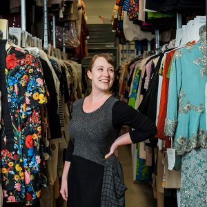 Image of a woman wearing a black dress standing among rows of hung clothing smiling over her shoulder.