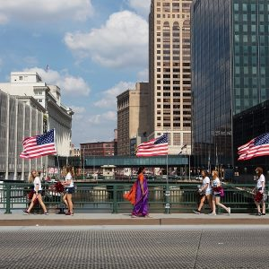 Image of a woman dressed in a sari walking across a bridge in front of American flags