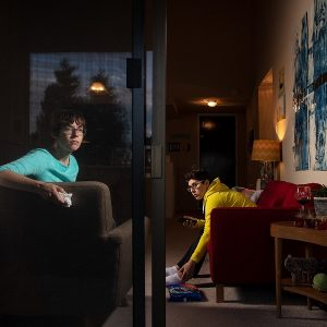Image of two women in an interior space. A woman in a yellow hoodie bends down to wipe her hands on her sock; a woman in a blue shirt looks out the window holding a sock.