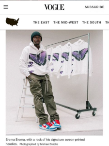 Screen shot of Vogue article featuring Brema Brema sitting in front of a rack of white sweatshirts with purple butterflies