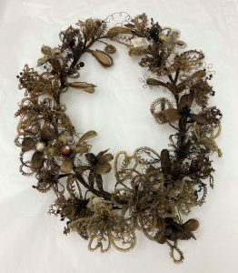 hair wreath made of blonde and brown hair sits on a white paper background