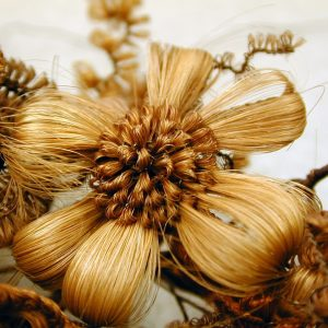Detail of hair wreath flower made of two colors of hair.