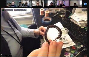 Screenshot of a zoom call in which the hands of a person hold up hairwork for the camera.