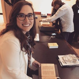 Woman in a white shirt and glasses sits at a table in front of medieval manuscripts and smiles at camera