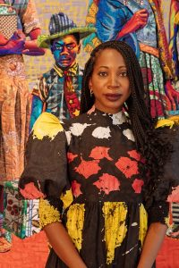 Bisa Butler stands in front of a colorful quilt. She wears a dress with large, puffy sleeves and her braided hair down.