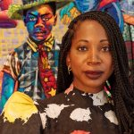Image of a woman, Bisa Butler, in front of a multi-colored artwork staring directly at the camera.