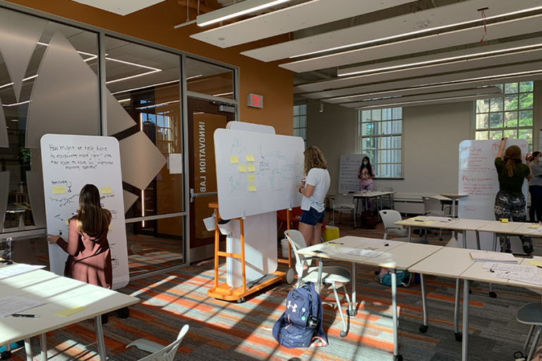 Image of students working in the Dorothy O'Brien Innovation Lab writing on white boards with post-it notes.