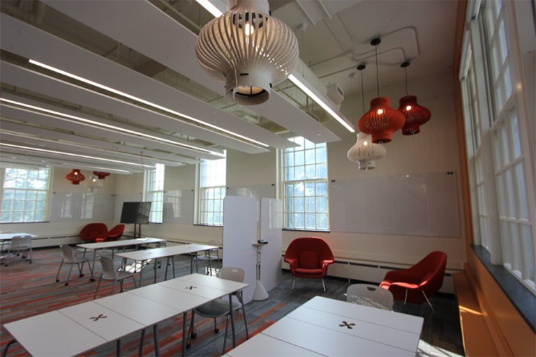 Photograph of the interior of the Dorothy O'Brien Innovation Lab with large windows, white walls, and red chairs.