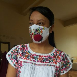 Woman wearing an elaborately embroidered face mask and shirt.
