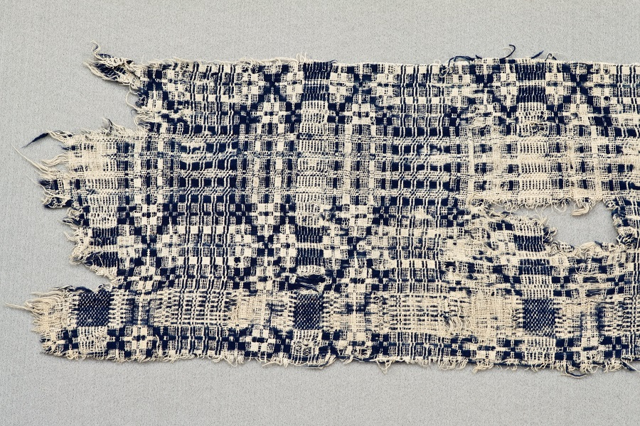 Image of a torn fragment of a woven blanket in blue and cream-colored fibers on a light grey background.