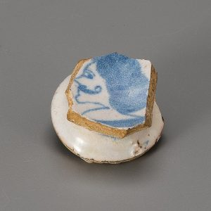 Photograph of a fragment of a ceramic delftware salt with blue and white glaze.