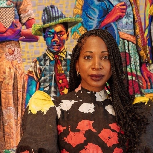 Bisa Butler stands in front of a colorful figural quilt hanging on the wall.