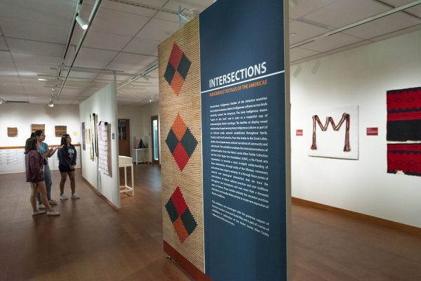 installation view of Intersections showing large text panel in foreground and students discussing a work in the background.