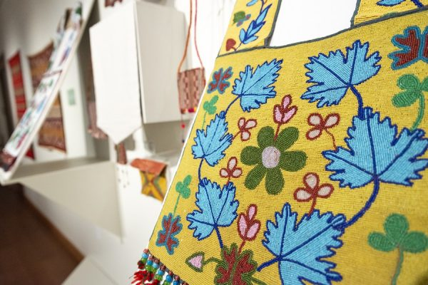 Close-up view of a beaded bandolier bag with floral imagery.