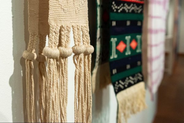 Close-up view of textiles hung on wall showing weave structure and knots.