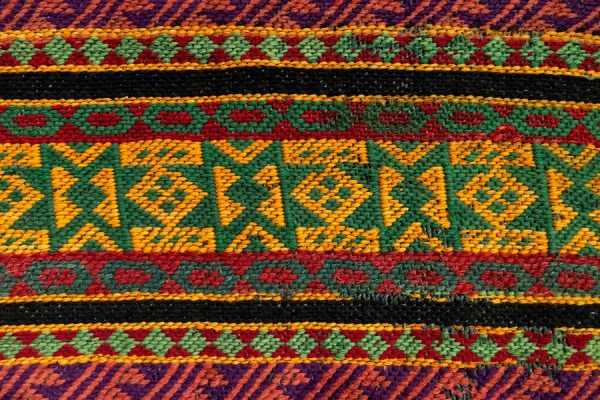 Close-up image of a brightly colored textile showing textures of weave.