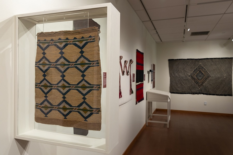 Installation view of Intersections showing a large display case holding a vertically-hung textile.