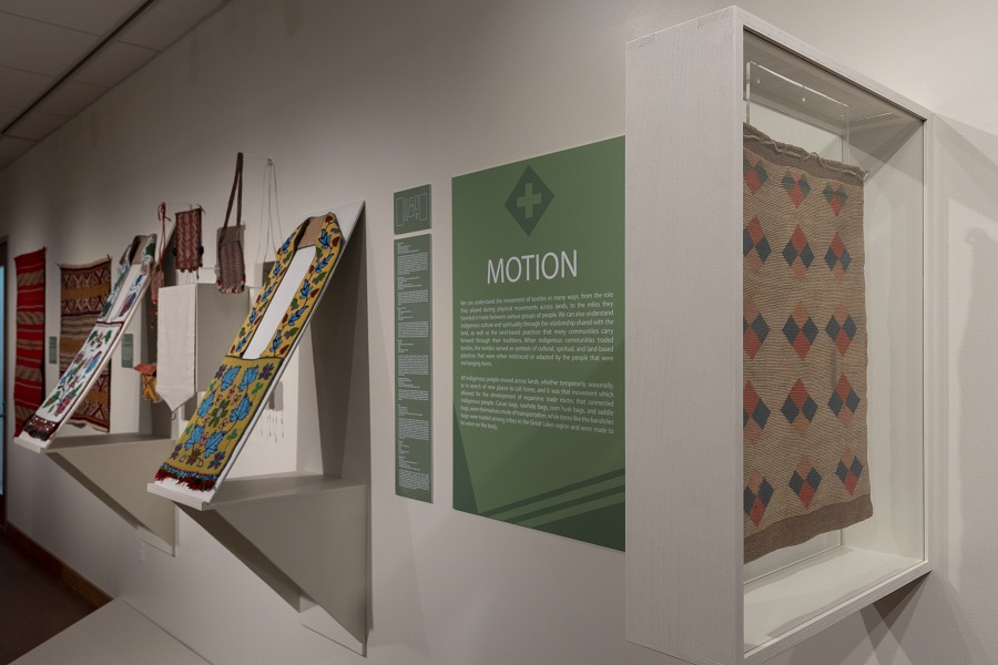 installation view of a textile exhibition showing beaded bandolier bags, installation panels with text, and a hung textile behind glass.