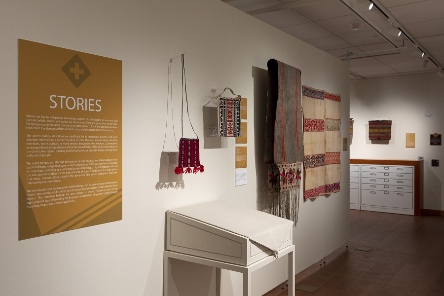 Photograph of textile installation showing wall didactic panels, mounted textiles, drawers, and covered display cases.