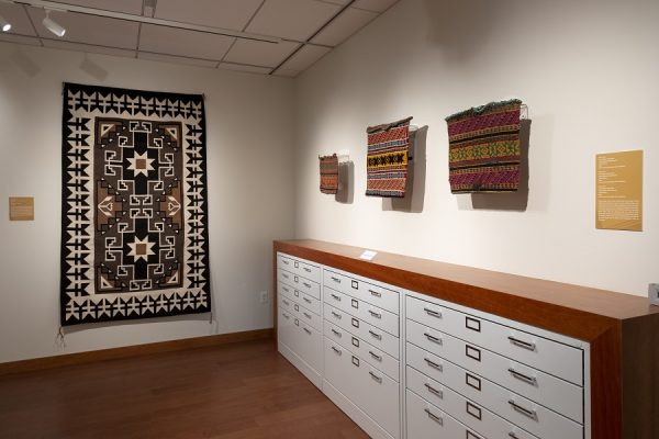 """view of """"Intersections"""" installation showing various textiles mounted on the walls above and next to storage drawers."""