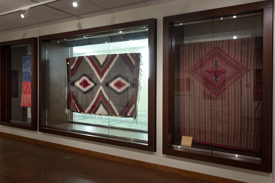 3 large textiles are installed vertically behind glass or between glass windows.