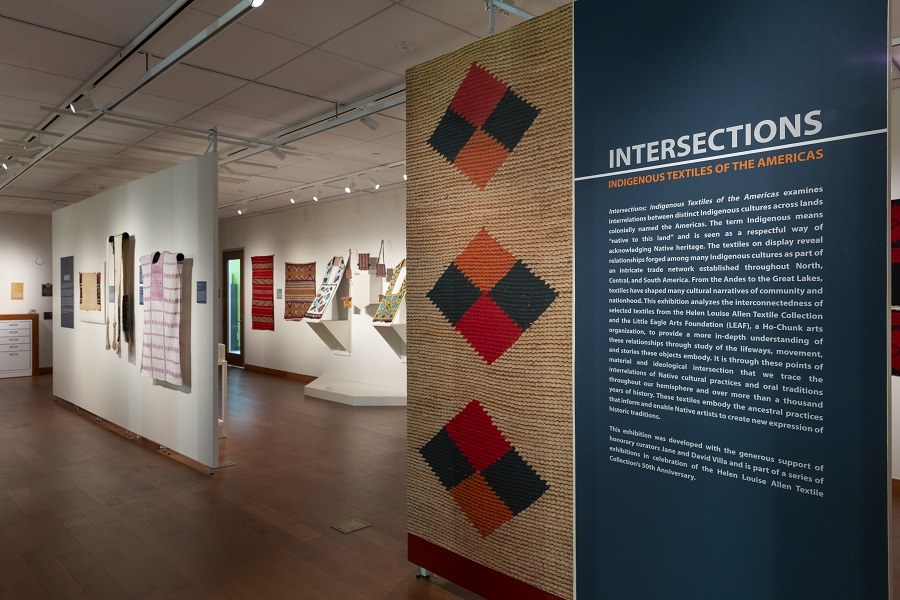 photograph of a textile installation showing a large colorful wall text panel in foreground and mounted objects in the background.