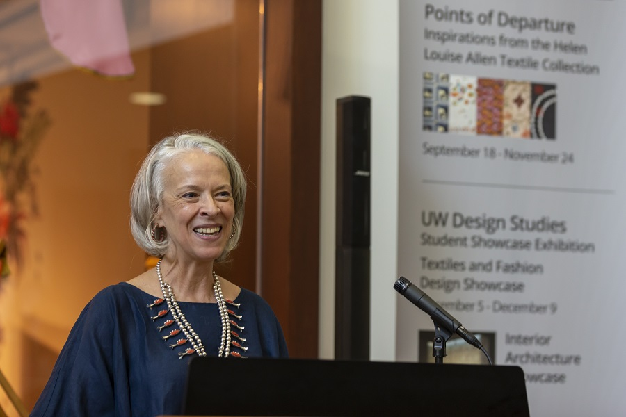woman in a blue shirt and dine silver necklace (Jane Villa) speaks at a podium and smiles.