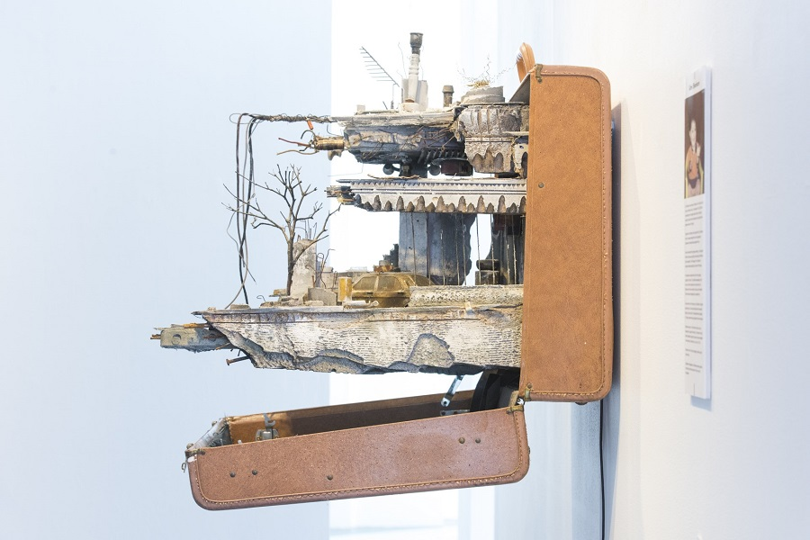 Image of a sculpture of a miniature bombed interior installed inside a suitcase.
