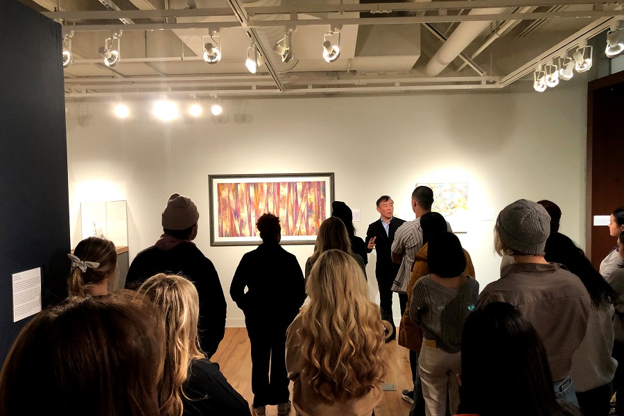Wei Dong speaking to a crowd in a gallery.