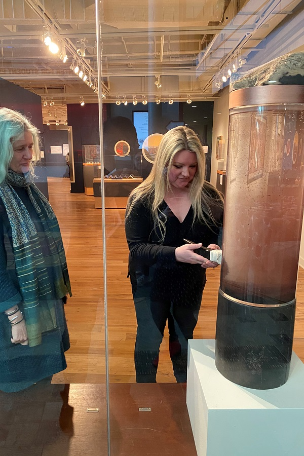 Two women interact with a large cylindrical sculpture.