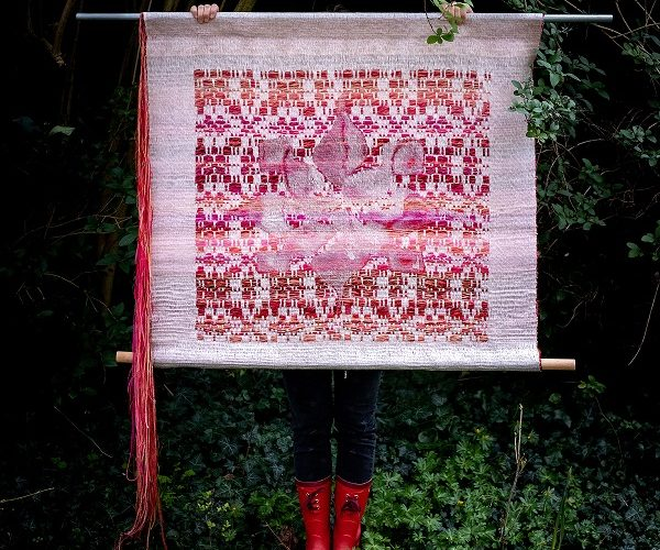 "Color photograph for exhibition ""Weaving Threads through Time and Space..."" Image depicts a mostly covered person standing outside in lush greenery wearing bright red rain boots and black pants holding up a large woven tapestry in pinks, reds, and whites in front of their face/body."