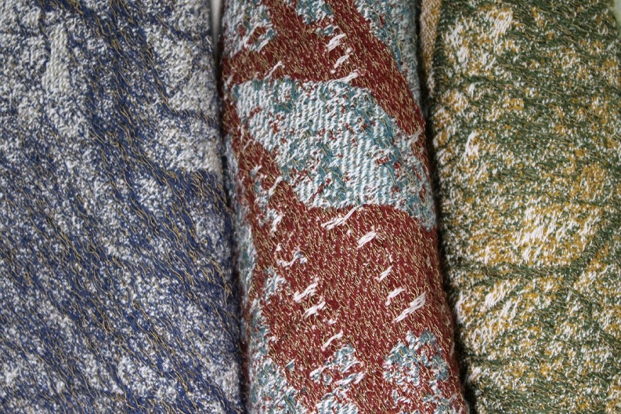3 rolled fabrics side-by-side in 3 different color ways: blue, marron, and green.