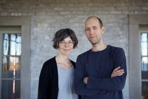 photograph of a man and woman (Shana McCaw & Brent Budsberg) wearing various shades of blue before a brick wall.