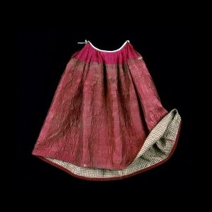 quilted petticoat in reds with checkered underskirt on a black background.