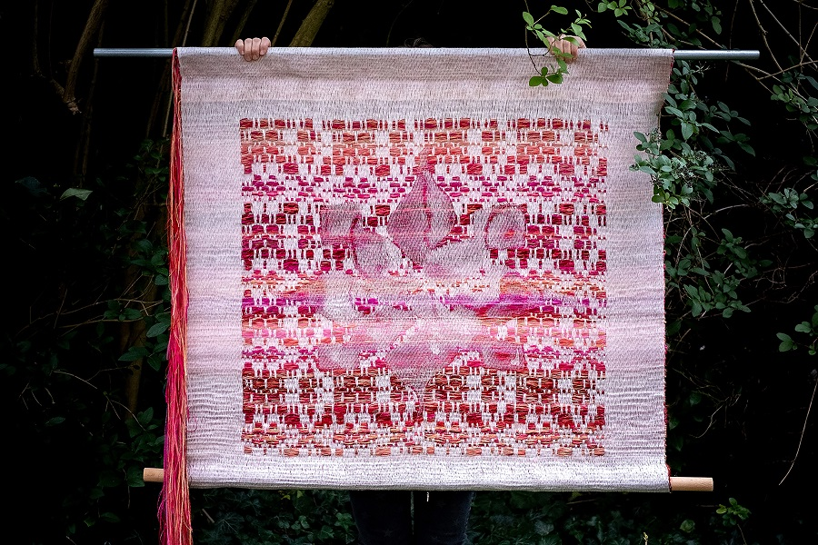 Color photograph depicting a mostly covered person standing outside in lush greenery wearing bright red rain boots and black pants holding up a large woven tapestry in pinks, reds, and whites in front of their face/body.