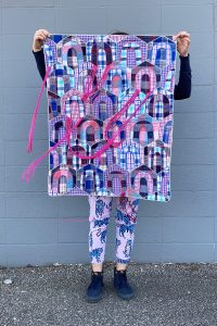 Person standing before a blue brick wall holding a quilt with beaded tassels blowing in the wind.
