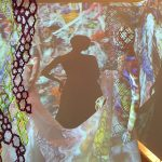 installation image of hung textiles and projections on a mannequin