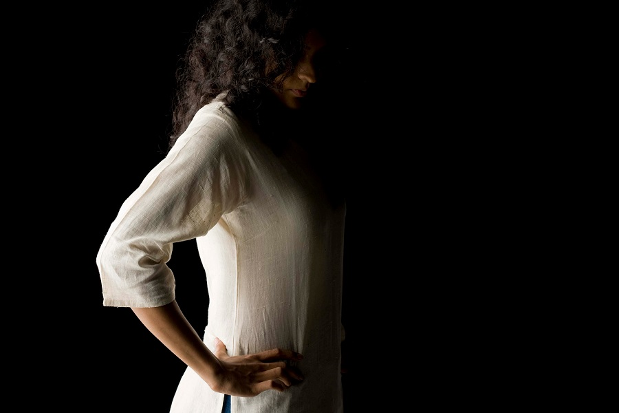 Woman in a darkened room wearing a white cotton kurta with her hands on her hips looking down.