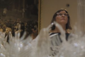 woman stands behind an elaborate installation of glass works.