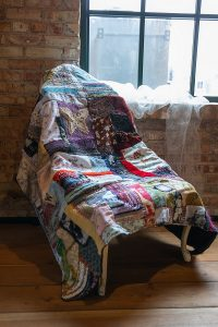 photograph of a quilt laid on a chair near a window.