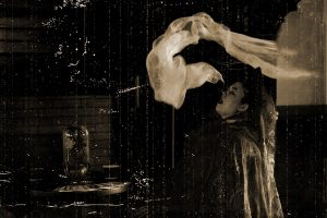 """grainy, sepia-toned black and white image of a woman in Victorian garb spewing white """"ectoplasm"""" from her mouth."""